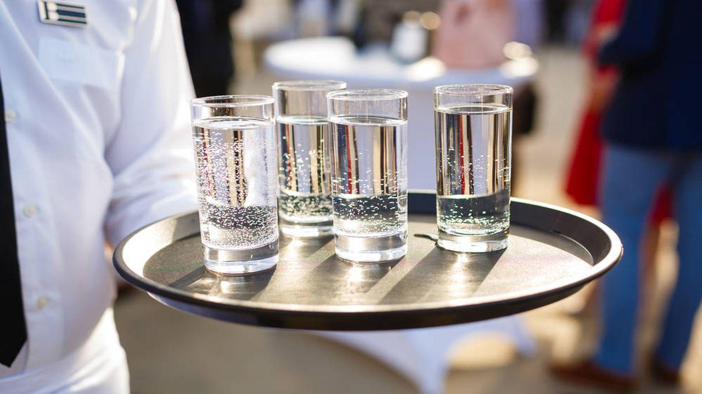 Un camarero sostiene una bandeja llena de vasos de agua.