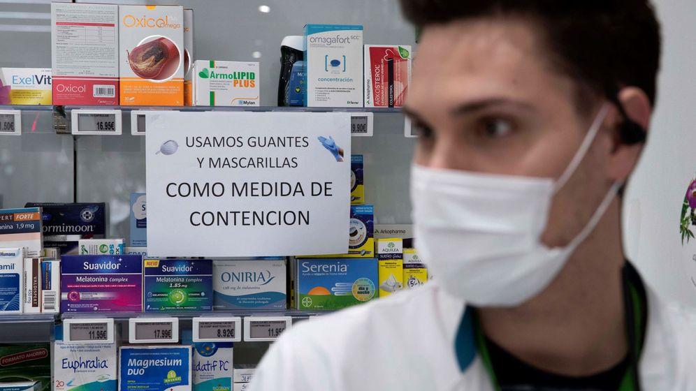 Foto: Un empleado de una farmacia con mascarilla para protegerse del coronavirus. (EFE)