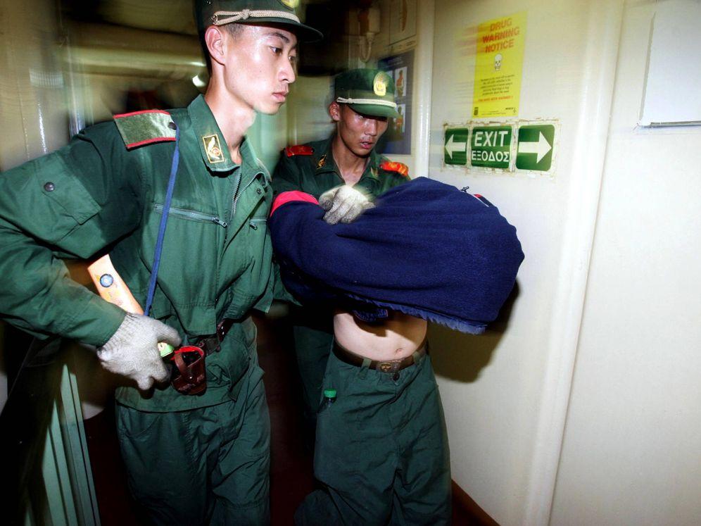 """Foto: Policías chinos detienen un inmigrante víctima de los """"cabeza de serpiente"""". (Reuters)"""
