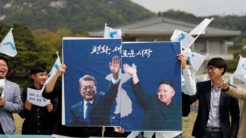 Estudiantes pro-unificación enarbolan posters del presidente surcoreano Moon Jae-in y el norcoreano Kim Jong Un en Seúl, el 26 de abril de 2018. (Reuters)