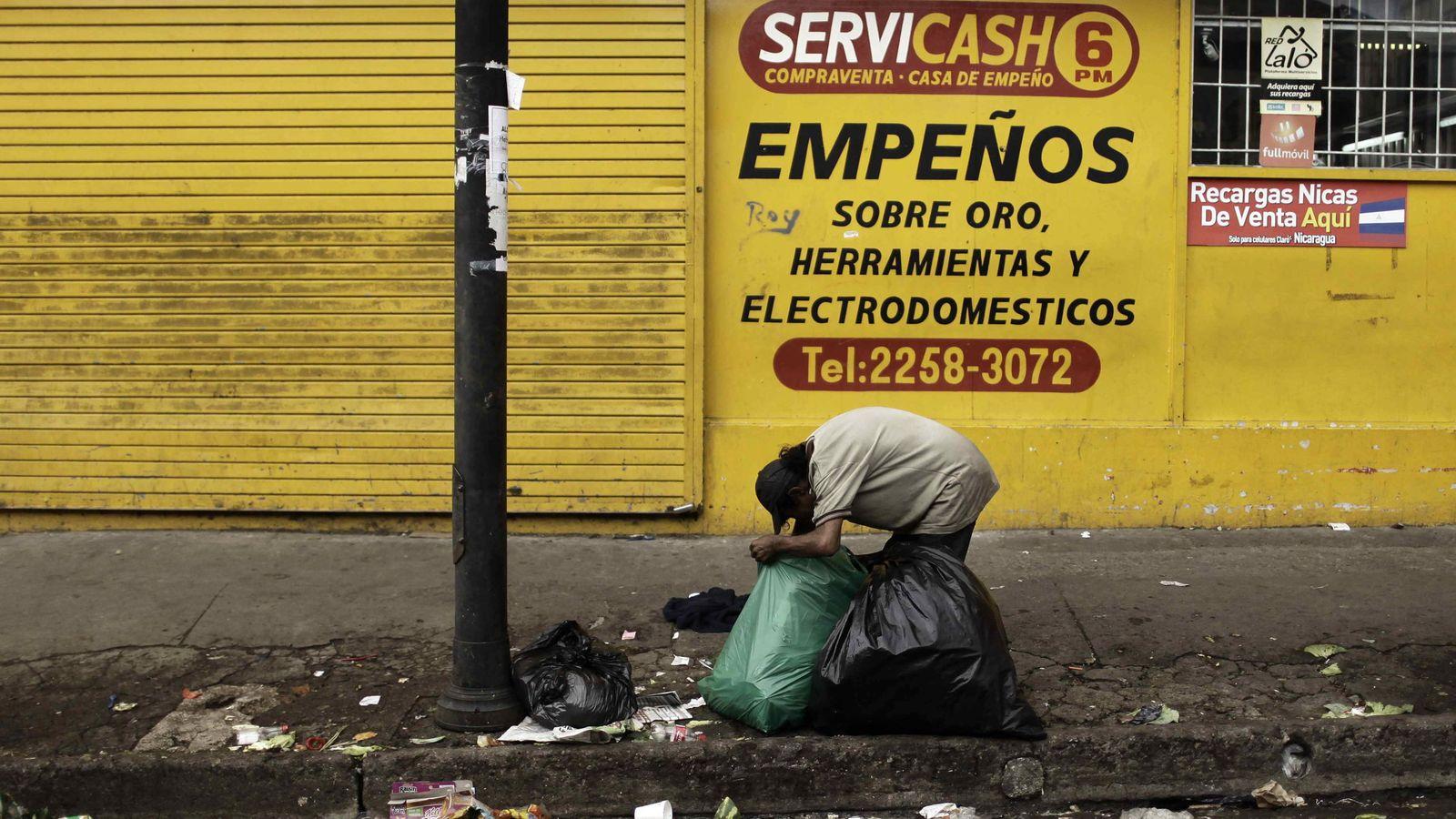 Foto: Un hombre hurga en bolsas de basura en la ciudadela Triángulo de Solidaridad, en San José (Costa Rica). (EFE)