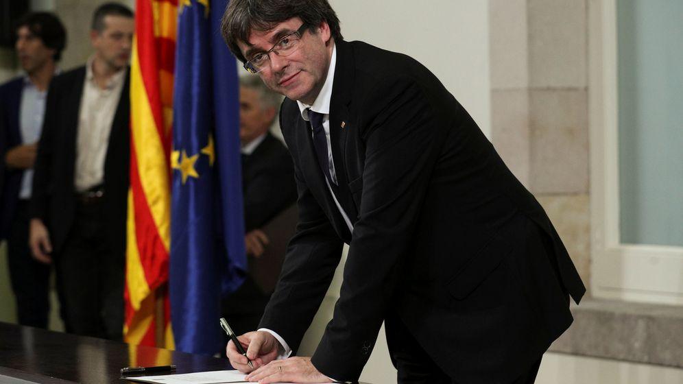 Foto: El presidente Puigdemont firma el documento de una futura declaración de independencia. (Reuters)