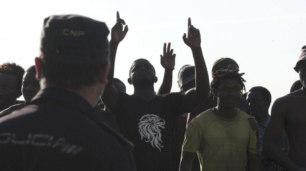 Foto: Agentes de la Policía Nacional frente a inmigrantes, en Ceuta. (EFE)