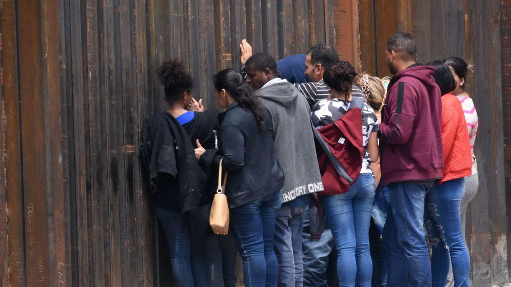 Foto: Migrantes centroamericanos se asoman a través del muro fronterizo, en Ciudad Juárez, México. (EFE)
