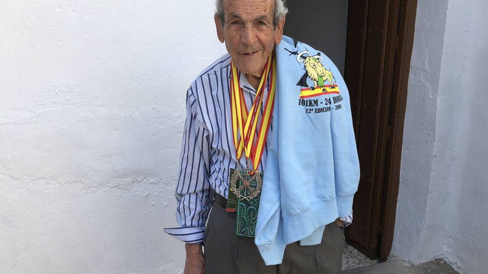 Foto: Súper Paco, en el patio de su casa de la barriada El Sexmo de Cártama, en Málaga, posando con una camiseta de los 101 kilómetros de Ronda y varias medallas de la competición. (Agustín Rivera)