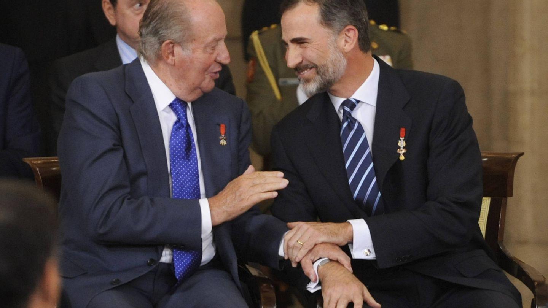 El rey Juan Carlos y el rey Felipe comparten confidencias durante un acto. (Getty)