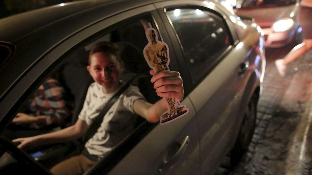 Foto: Un fan sostiene una réplica de un Oscar mientras pasea en coche (Reuters)