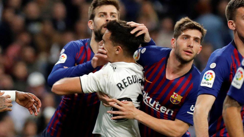 Foto: Reguilón es sujetado por Sergi Roberto y Piqué en un lance del partido de Liga. (EFE)