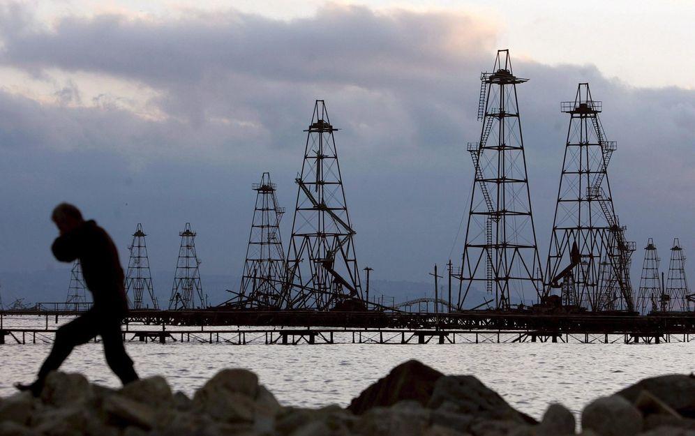 Foto: Un trabajador pasa frente a unas torres de extracción de crudo en el Mar Caspio, cerca de Bakú, Azerbaiyán (EFE)