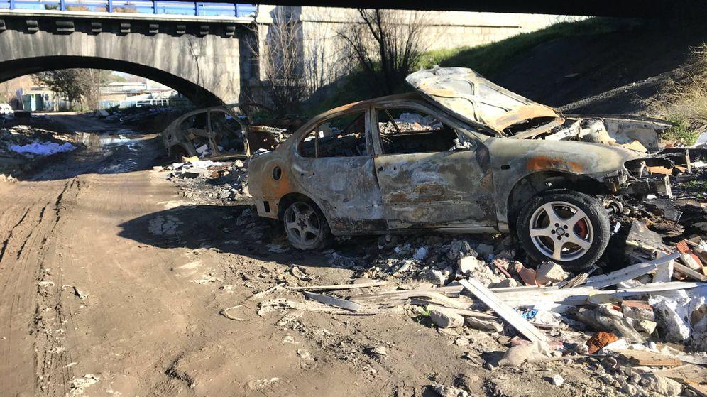 Foto: Dos coches calcinados y montones de basura en el río Guadarrama. (Guillermo Cid)