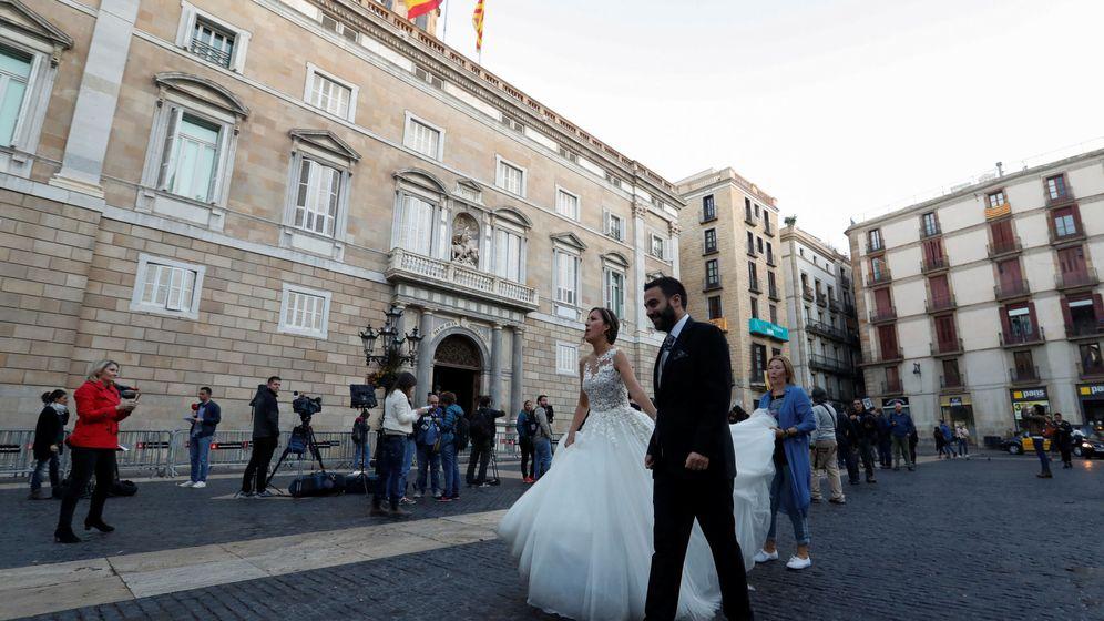 Foto: Una pareja de recién casados pasa por delante del Palau de la Generalitat. (Reuters)