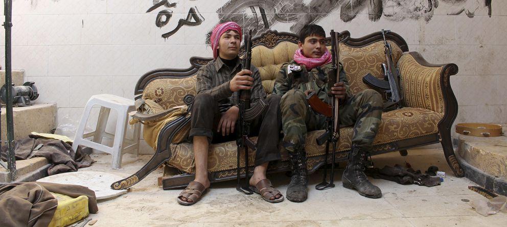 Foto: Dos jóvenes combatientes del Ejército Libre de Siria posan en la Ciudad Vieja de Alepo. En la pared se lee: Dios, Siria, Libre. (Reuters)