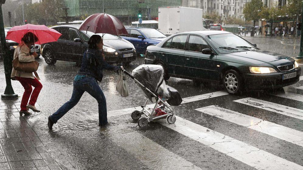 Foto: Dos personas pasan por un paso de peatones en Pamplona durante un día lluvioso. (EFE)