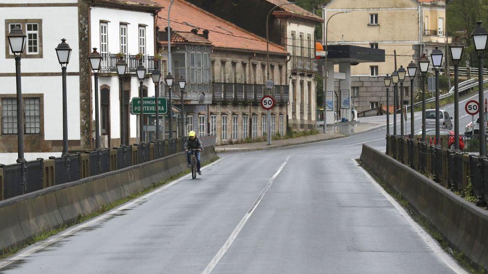 Foto: Un vecino de Pontecesures pasa hacia Padrón. (EFE)