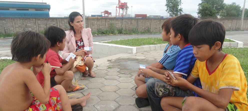 Foto: Una trabajadora social de Protect con un grupo de niños en Sihanoukville (Camboya). (Action pour les Enfants)