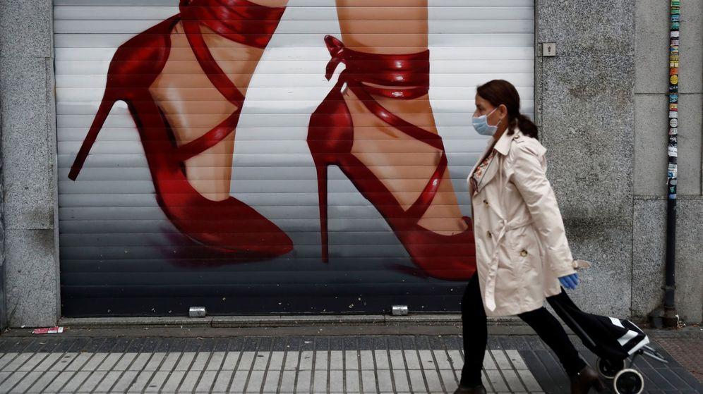 Foto: Una mujer que va a hacer la compra pasa ante el cierre de un negocio cerrado en Madrid. (EFE)