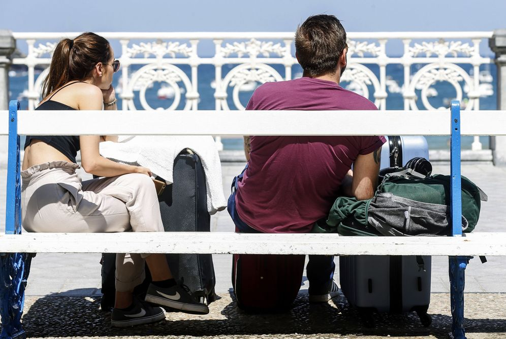Foto: Dos turistas descansan con sus maletas en el paseo de La Concha de San Sebastián. (EFE)