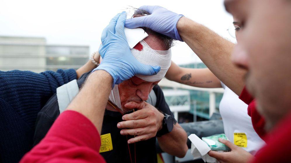 Foto: Un sanitario atiende a un manifestante herido después de las cargas de los Mossos d'Esquadra en El Prat. (EFE)