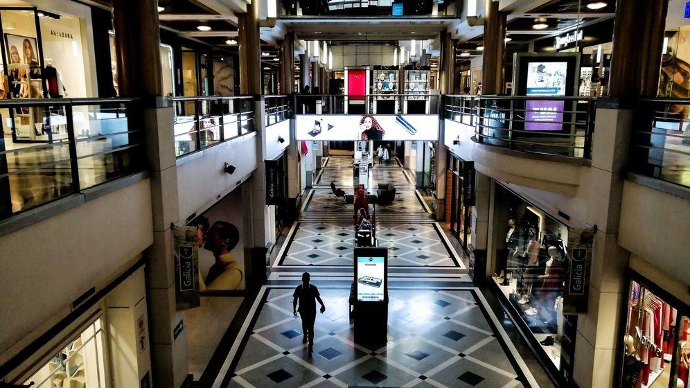 Foto: Un hombre pasea por un centro comercial con los comercios cerrados. (EFE)