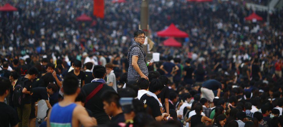 Foto: Un hombre observa a los manifestantes mientras bloquean este martes el distrito financiero de Hong Kong (Reuters).