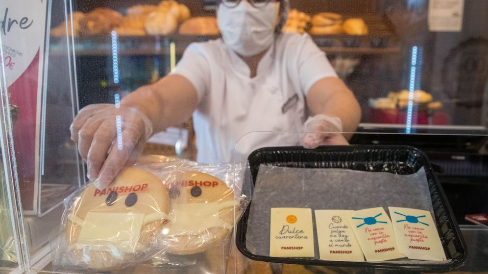 Foto: La dependienta de una pastelería-panadería muestra las galletas con mascarilla. (EFE)