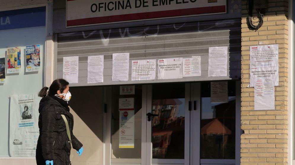 Foto: Una mujer con mascarilla pasa ante una oficina de empleo en Madrid. (EFE)