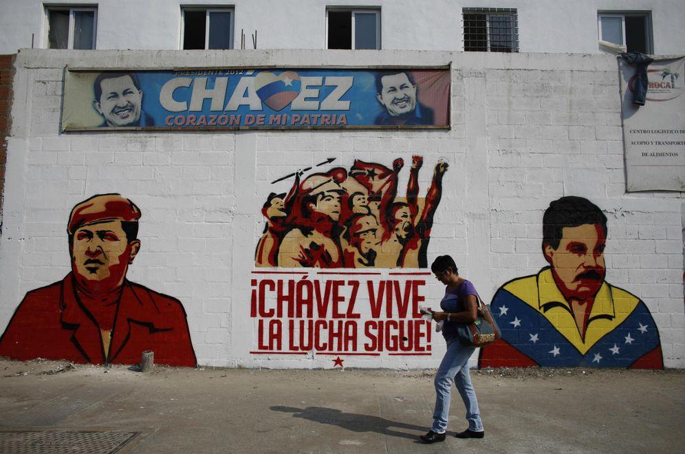 Foto: Una mujer pasa frente a un mural de los presidentes Hugo Chávez y Nicolás Maduro (Reuters)