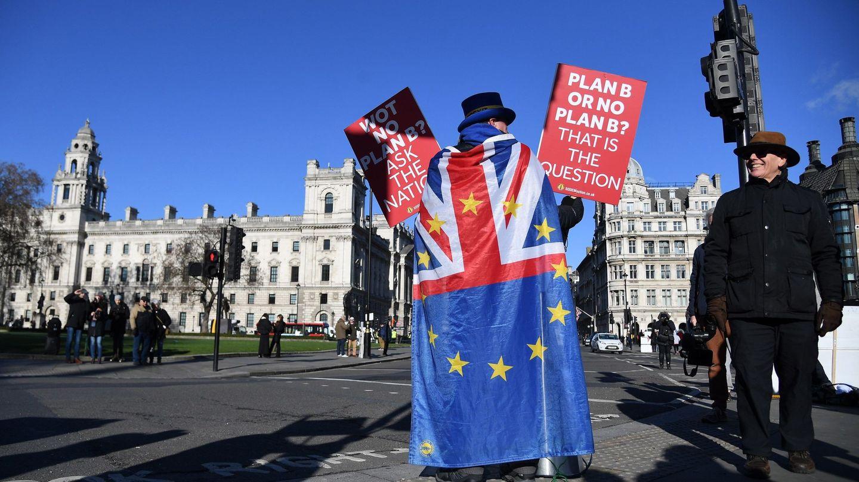Un activista en contra del Brexit sostiene pancartas ante el edificio del Parlamento británico, en Londres. (EFE)