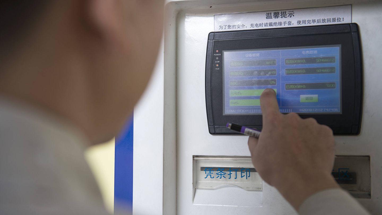 Un empleado de Potevio calcula el precio de la carga del autobús que conduce Guo Peiming. (Z. Aldama)