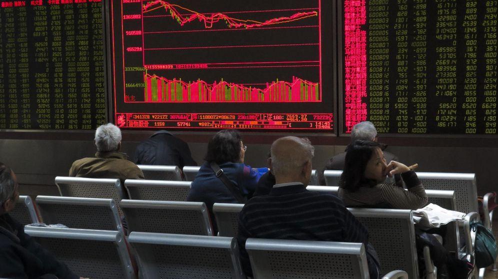 Foto: Inversores siguen la evolución bursátil en una casa de corretaje en Pekín (China). (EFE)