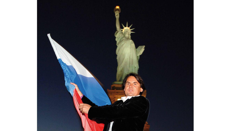 Foto: Rustam Tariko, fundador de las vodkas Russian Standard, ondea una bandera rusa ante la Estatua de la Libertad en Estados Unidos. (Getty Images)
