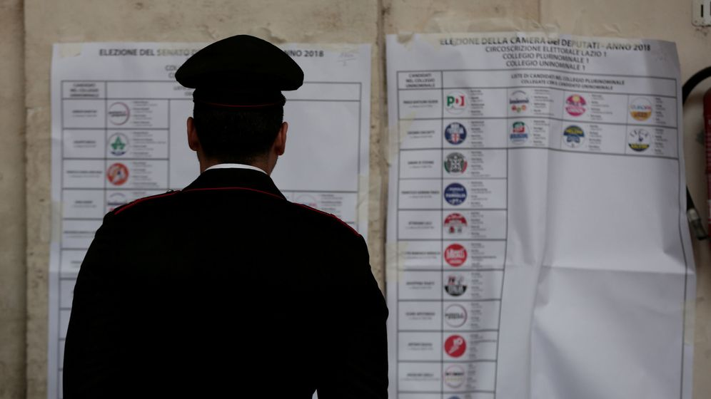 Foto: Un policía mira un cartel en un colegio electoral en Roma, ayer, 4 de marzo. (Reuters)