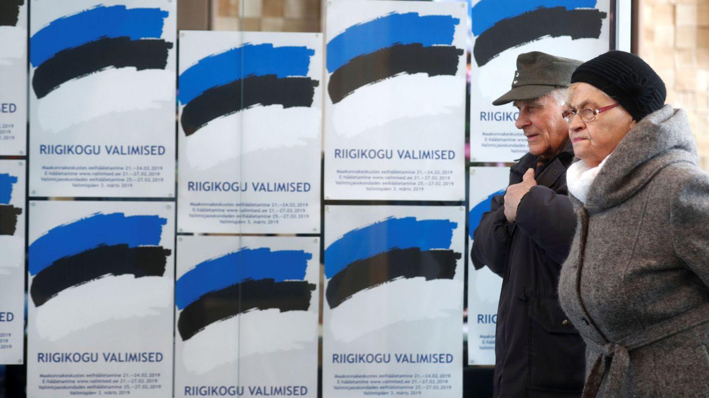 Dos personas pasan frente a unos carteles electorales en Parnu, Estonia, el 3 de marzo de 2019. (Reuters)