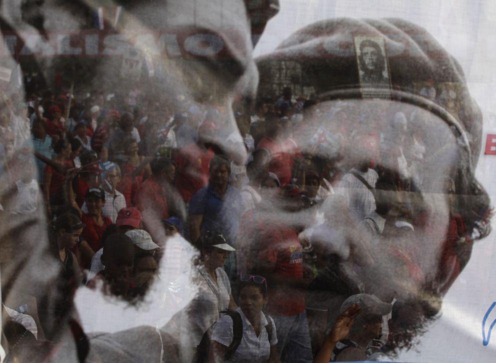 Foto: Cubanos tras un póster de Fidel Castro y Ernesto Che Guevara durante una marcha en el Primero de Mayo, en La Habana (Reuters).