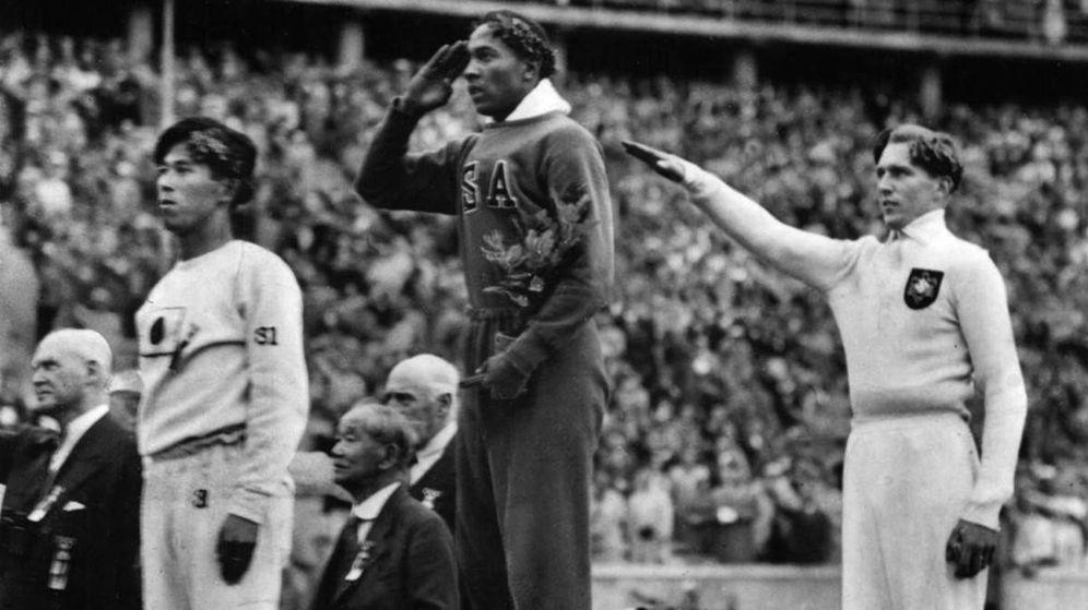 Foto: El atleta estadounidense recibe la medalla de oro en los Juegos Olímpicos de Berlín de 1937. Tra él, un corredor alemán hace el saludo nazi.
