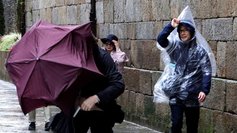 Foto: Turistas japoneses, luchando por no perder sus paraguas este domingo en Santiago de Compostela. (EFE)