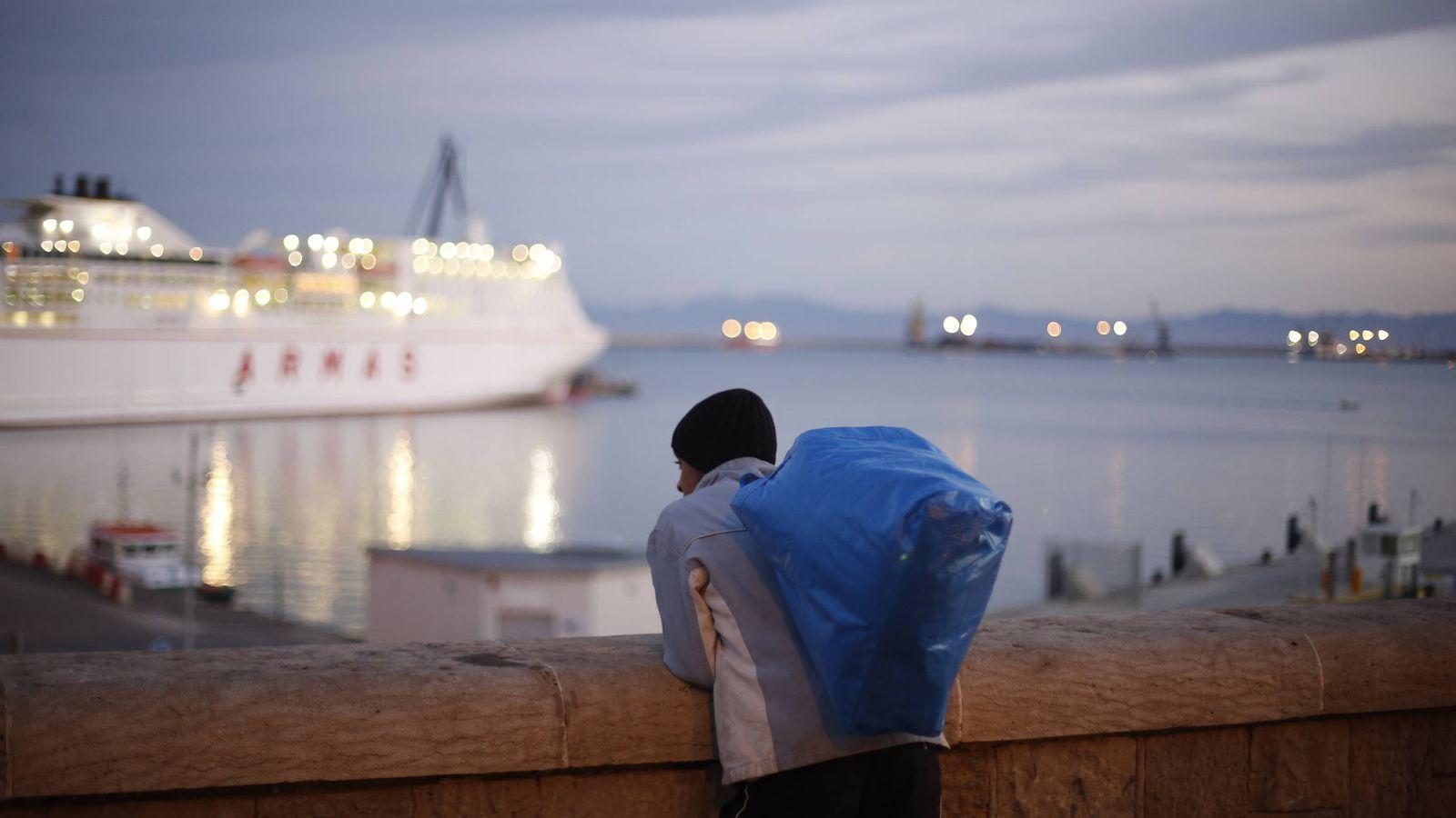 Foto: Un joven marroquí observa un barco a punto de partir del puerto de Melilla. (Reuters)