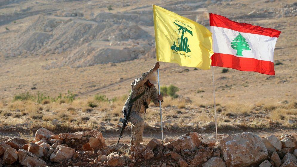 Foto: Un combatiente de Hezbollah despliega su bandera y la del Líbano en las montañas de Arsal, a finales de julio. (Reuters)