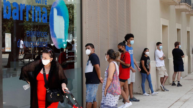 Ciudadanos del barrio de Collblanc de L,Hospitalet de Llobregat (Barcelona), guardan cola frente a uno de los dispositivos para hacer PCR. (EFE)