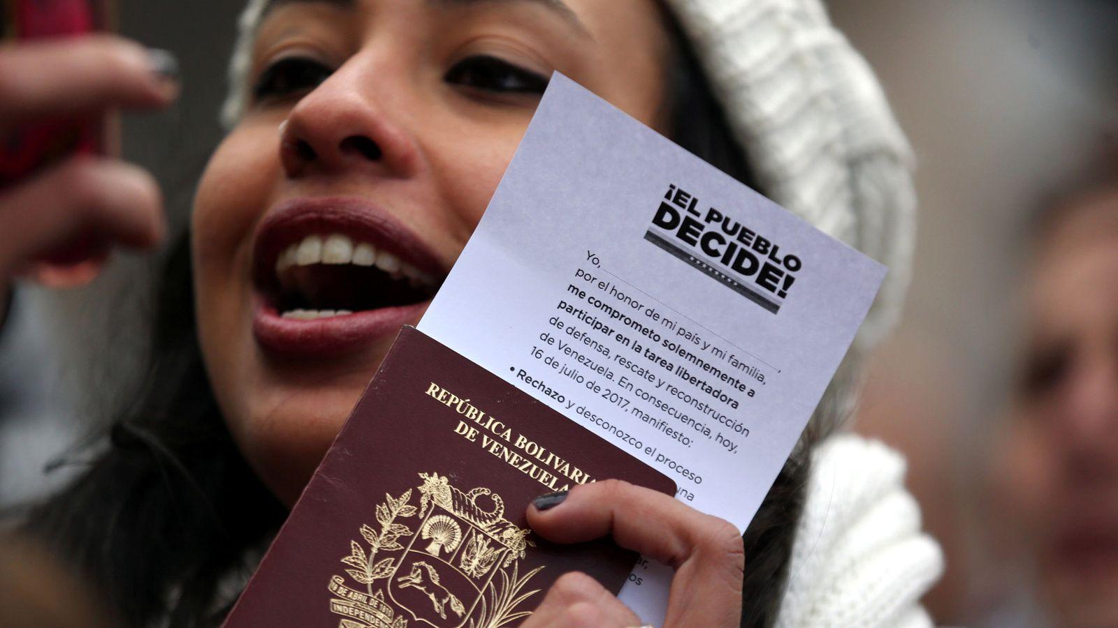Foto: Una joven venezolana en Buenos Aires muestra su pasaporte tras votar en el plebiscito no oficial contra Maduro, el 16 de julio de 2017. (Reuters)