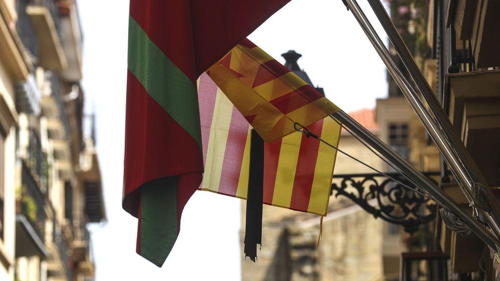 Foto: Una bandera catalana con crespón negro junto a una ikurriña en la puerta de una sociedad gastronómica de la Parte Vieja de San Sebastián. (EFE)