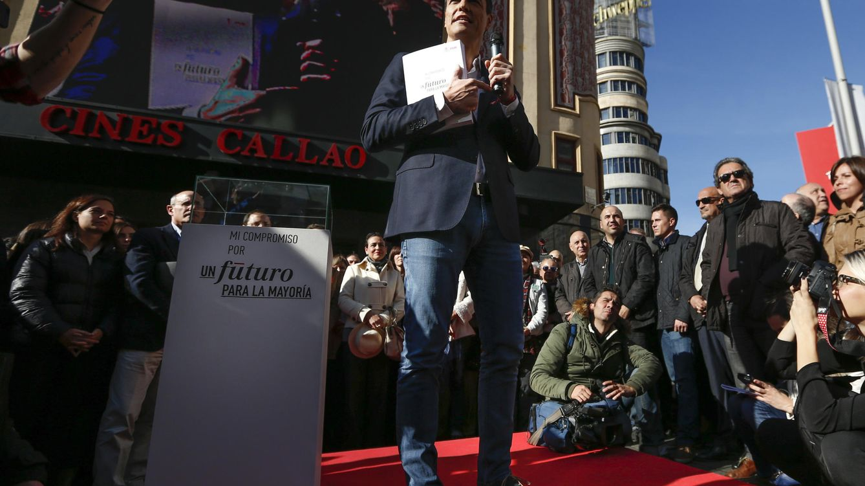 Foto: Pedro Sánchez, micrófono en mano, exhibe el programa del PSOE, tras firmarlo como contrato con los ciudadanos en la plaza del Callao de Madrid, este 9 de diciembre. (EFE)