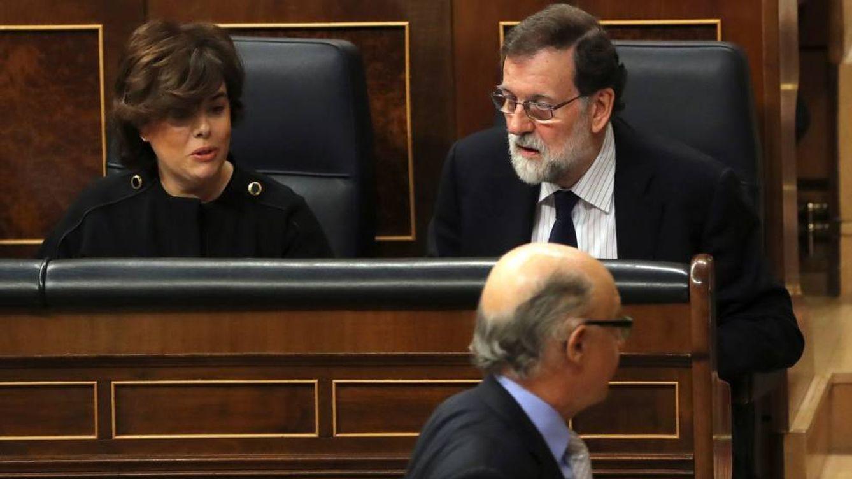 Foto: El exministro de Hacienda Cristóbal Montoro (abajo) pasa ante el expresidente del Gobierno Mariano Rajoy y la exvicepresidenta Soraya Sáenz de Santamaría en una sesión de control al Gobierno. (EFE)