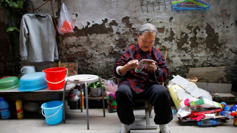 La señora Zhong, una inmigrante rural, remienda zapatos en el patio de su casa en el extrarradio de Pekín, el 1 de octubre de 2017. (Reuters)