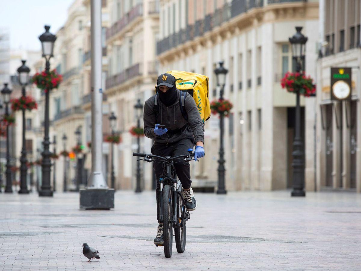 Foto: Repartidor, en una desierta calle Larios de Málaga. (EFE)