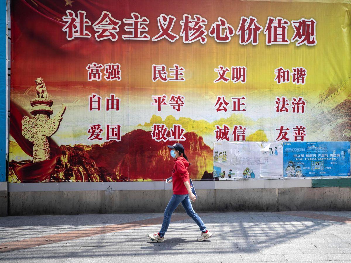 Foto: Una mujer en Guangzhou, delante de un cartel con los 12 valores principales del socialismo chino. (Alex Plavevski/EFE)