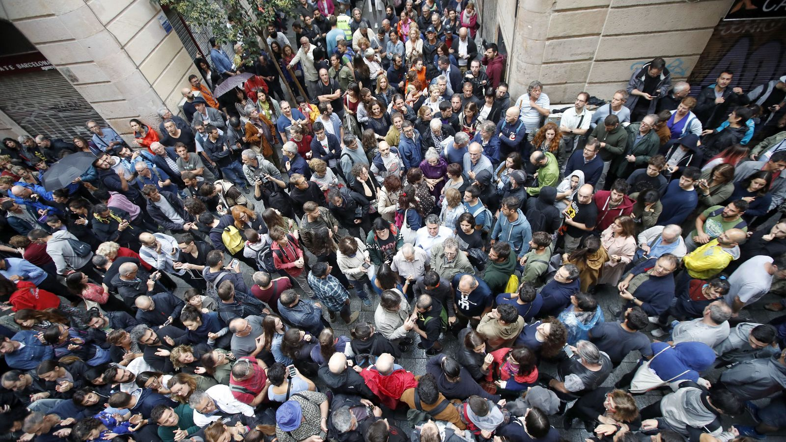 Foto: Numerosas personas esperan a las afueras del colegio Cervantes de Barcelona el 1-O. (EFE)