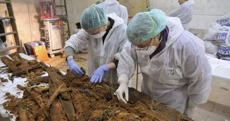 Foto: Dos especialistas analizan parte de los restos hallados en la cripta de las trinitarias. (REUTERS)