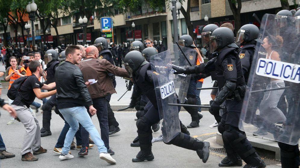 Foto: Agentes de la Policía Nacional intentan retirar a los concentrados en el instituto IES Tarragona el 1-O. (EFE)
