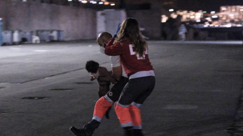 Dos voluntarios de Cruz Roja intentan reanimar a la niña en el muelle de Arguineguín (Gran Canaria). (EFE)